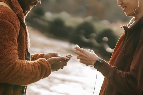 棕色長袖襯衫與白襯衫的男人手牽著手的人