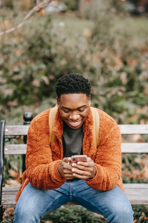 Young black man smiling while using smartphone in city park