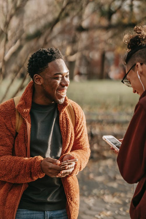 Delighted young multiracial male friends wearing warm clothes standing in autumn park and laughing while browsing modern smartphones