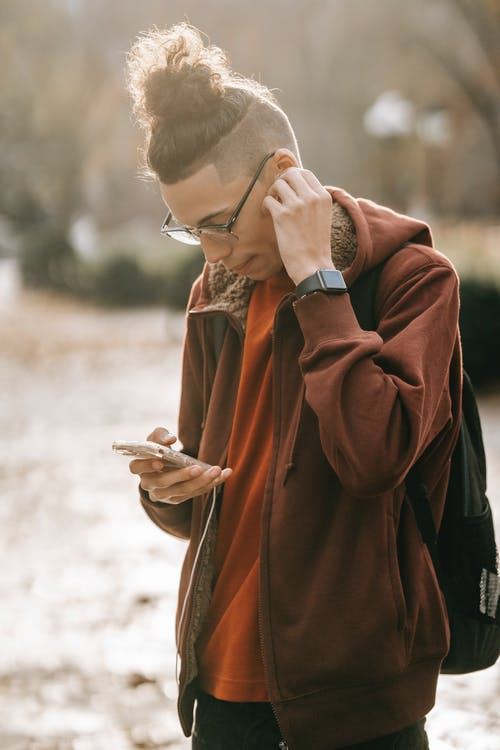 Side view of young confident ethnic male wearing hoodie standing in city park and putting earphones of smartphone in ears