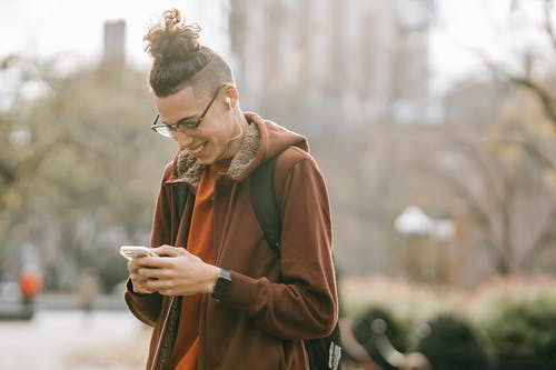Young ethnic guy with backpack smiling while listening to music on smartphone