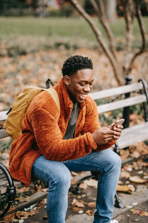 Side view of young positive African American man with backpack sitting in park on autumn day and using modern smartphone