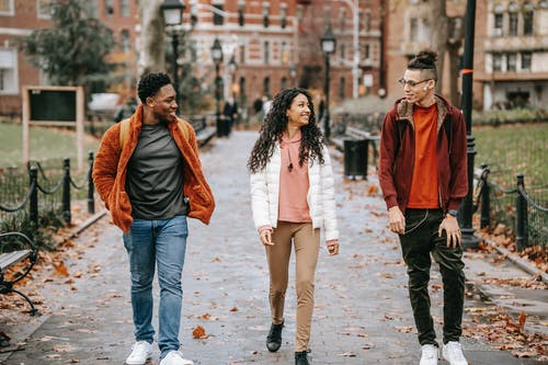 Positive young ethnic guys with female friend walking along pathway in city