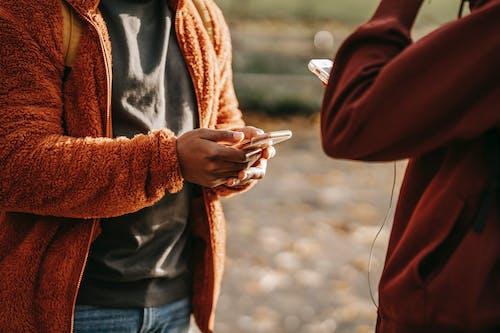 Crop friends browsing smartphones on street