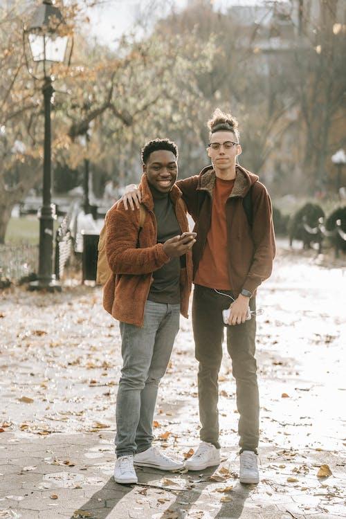 茶色のコートを着た男性と茶色のコートを着た女性の横に立っている青いデニムジーンズ