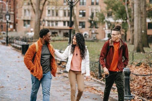 Happy diverse friends walking in fall park