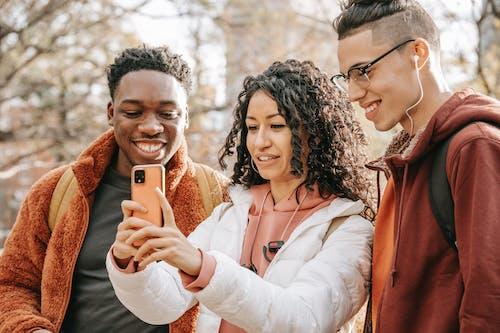 Smiling diverse friends making selfie on smartphone