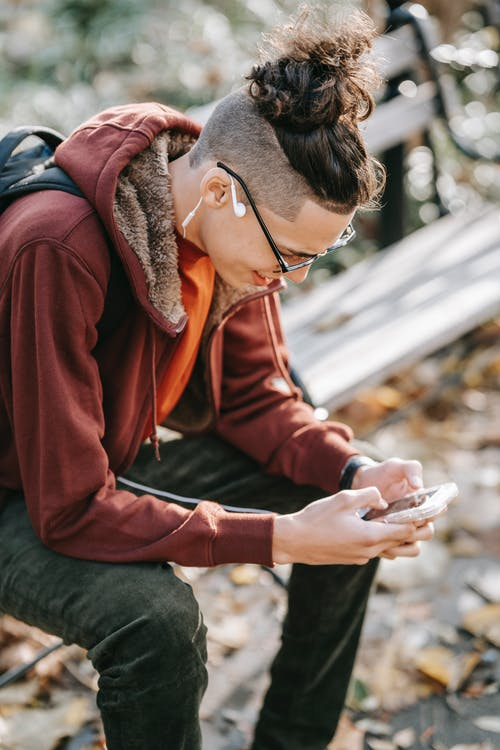Excited male with modern hairstyle sitting on bench in autumn park and messaging on mobile phone while looking at screen