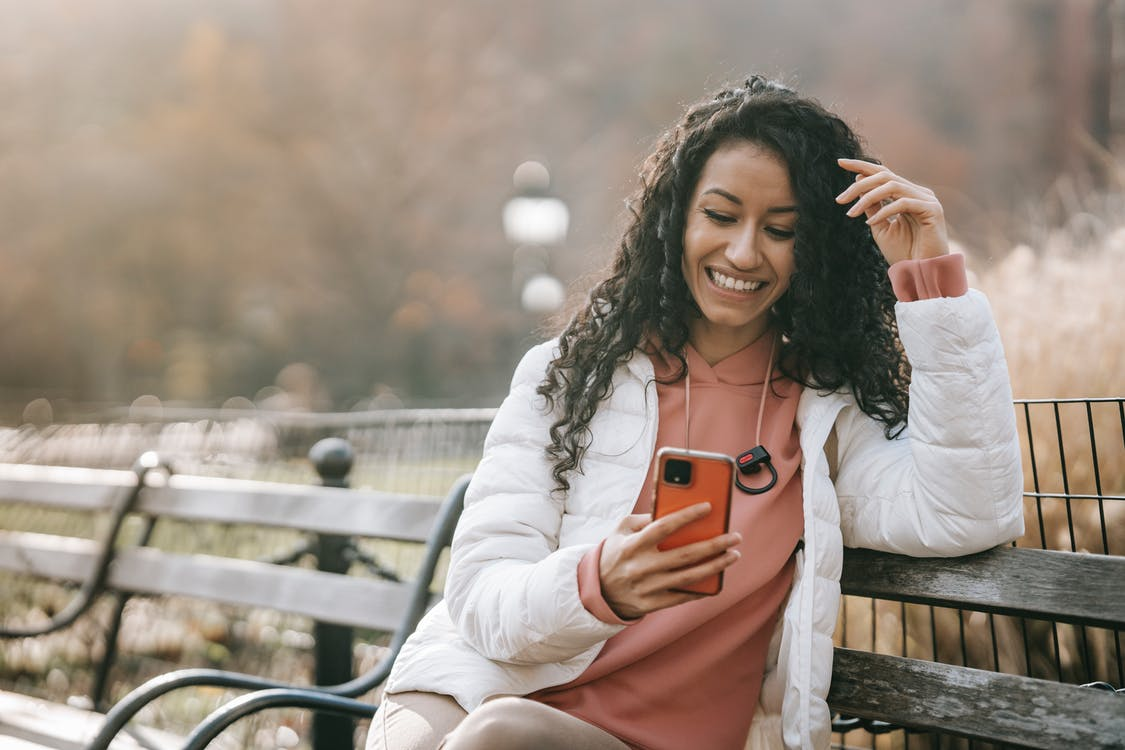 Cheerful Latin American woman with smartphone, finance on phone app