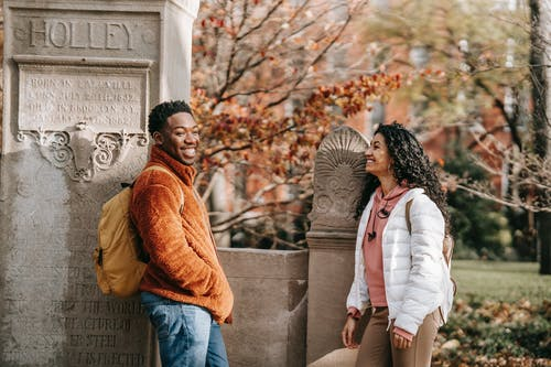 Happy multiracial couple in trendy clothes standing in fall park and laughing while spending time together