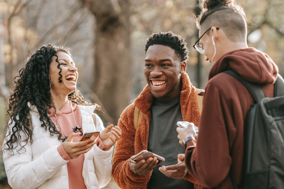 Laughing diverse friends with smartphones in park