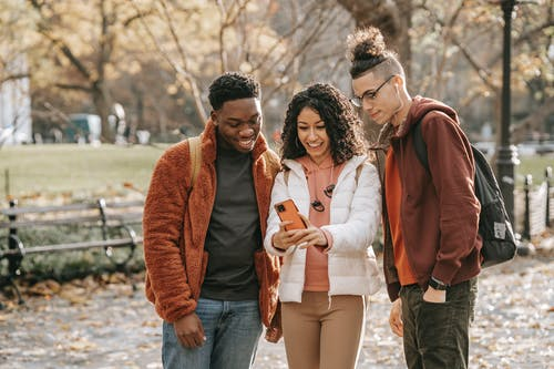 Group of diverse friends in stylish outfits standing in fall park with smartphone and taking selfie while smiling and looking at screen