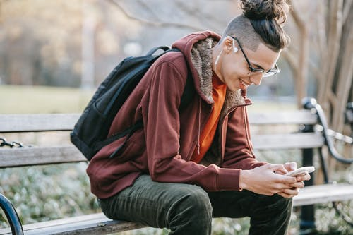 Cheerful man with smartphone in park