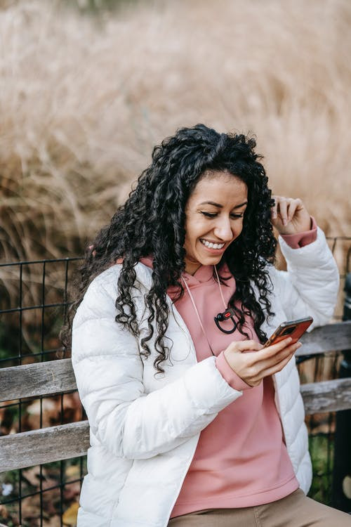 Cheerful Latin American female with curly hair browsing mobile phone while sitting on wooden bench and looking at screen