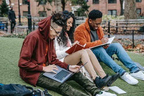 Happy multiracial group of students in casual clothes sitting together on grass and studying with laptop and books