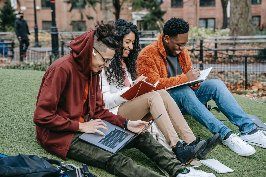 Cheerful multiracial group of students in casual clothes sitting together on the grass and studying with laptop and books