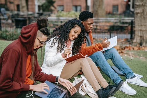 Multiethnic students studying together in fall park