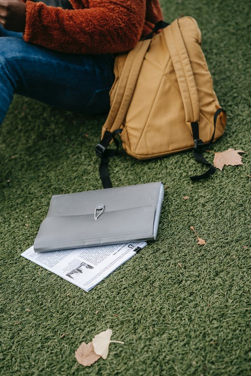 Crop anonymous person in casual clothes with backpack and folder sitting on grass and studying