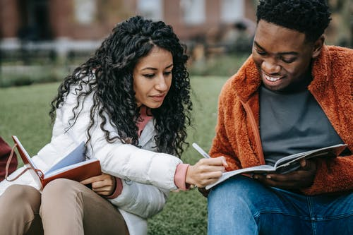 Cheerful multiethnic students studying together in campus park