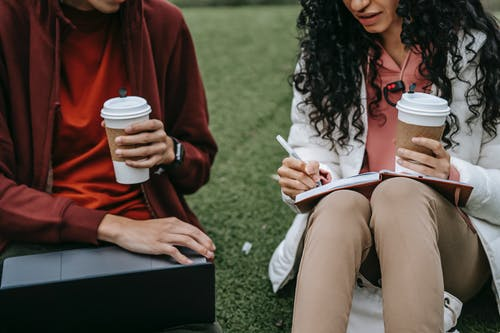 Unrecognizable students with takeaway beverage browsing laptop and writing in copybook while doing homework together on grassy ground on street