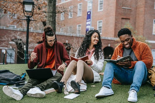 Full body of happy diverse students with notebooks and laptop sitting on grassy lawn on campus of university while studying together