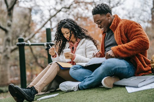 Multiethnic couple with copybooks studying on grassy lawn