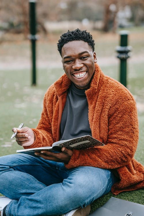 Smiling African American male student with copybook looking at camera while sitting on grassy lawn during homework preparation on blurred background