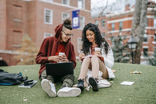 Cheerful multiethnic students with laptop and copybook studying on grassy lawn