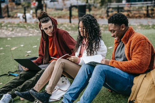 Group of multiracial classmates with notebooks browsing laptop and sitting on grassy lawn while doing homework assignment together on street