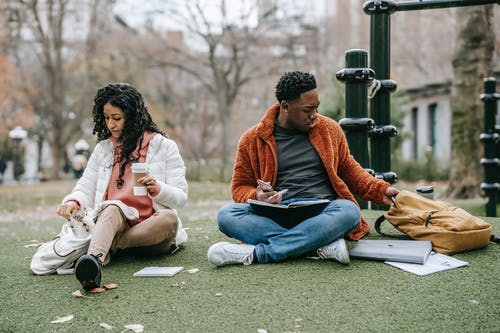 Multiethnic couple with backpacks sitting on lawn while preparing for classes