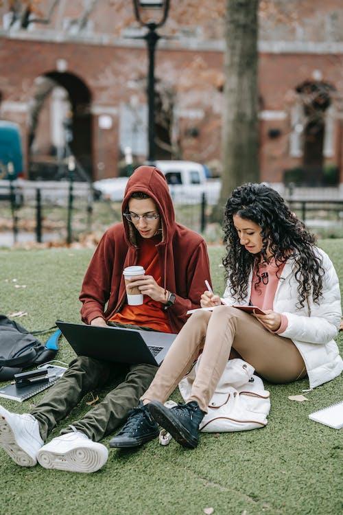 Sırasında Siyah Dizüstü Bilgisayar Kullanarak Yeşil çim Sahada Oturan Beyaz Uzun Kollu Gömlekli Kadın