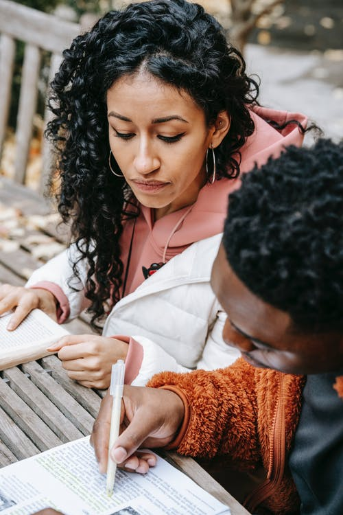 From above of focused ethnic female student sitting at wooden table with black man highlighting text in book while studying together on terrace