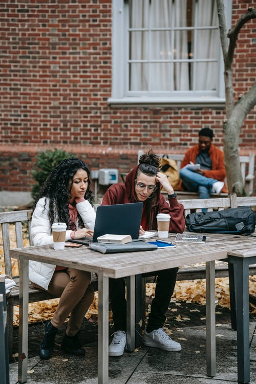 Full body of multiethnic students surfing netbook at table with takeaway coffee while studying together on street with distant black friend
