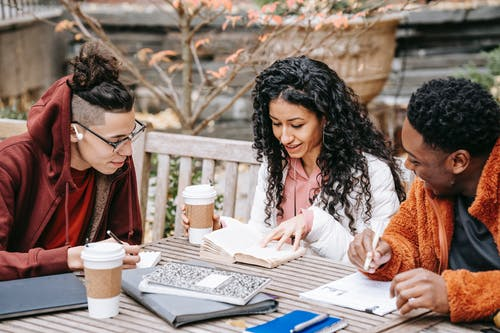 Cheerful multiethnic students with notebooks studying at table