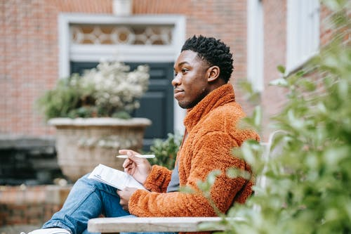 Side view of thoughtful African American male student writing on paper while sitting on bench near building on street during homework preparation on blurred background
