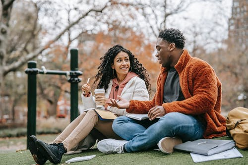 Multiethnic couple with notebooks communicating on grassy lawn while studying together