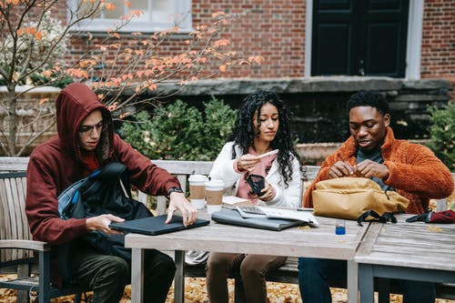 Group of multiethnic students sitting at wooden table with takeaway coffee while putting notebook in rucksack during studies on terrace