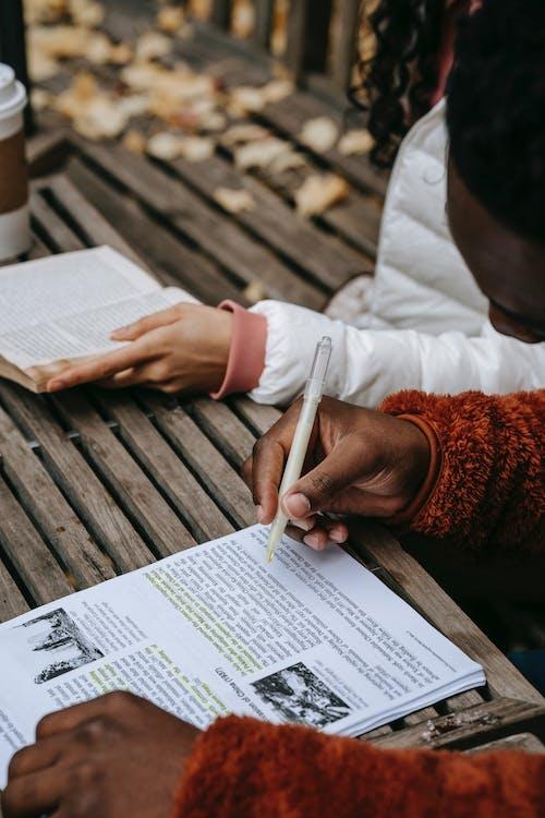 Crop black man taking notes in book