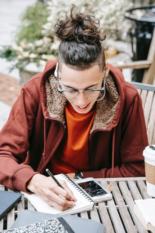 Focused male student with eyeglasses taking notes in notepad while sitting at wooden table with smartphone on street while doing homework