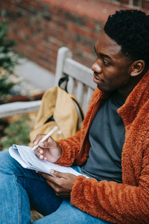 From above of crop African American male in warm clothes writing in organizer while looking away on blurred background