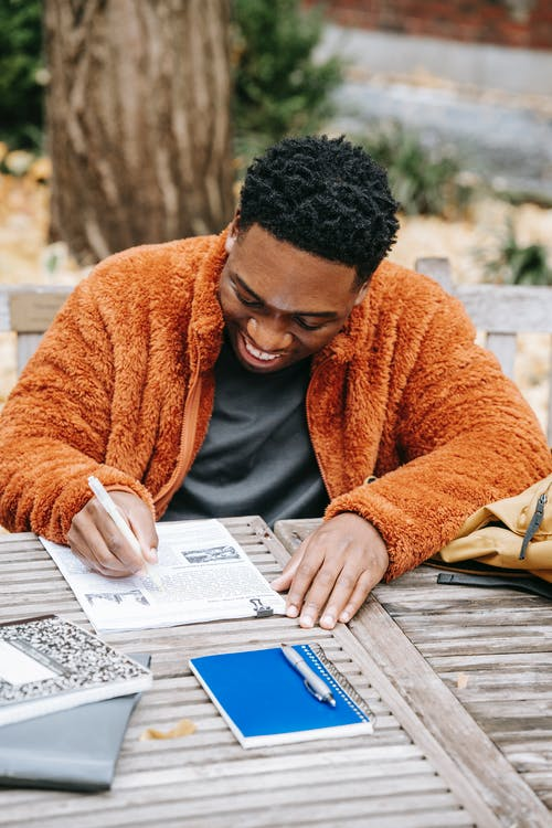 From above of cheerful young African American male smiling while studying and examining report on paper at table with planner