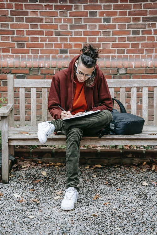 Full body of smart young student writing on paper while studying and preparing for exam