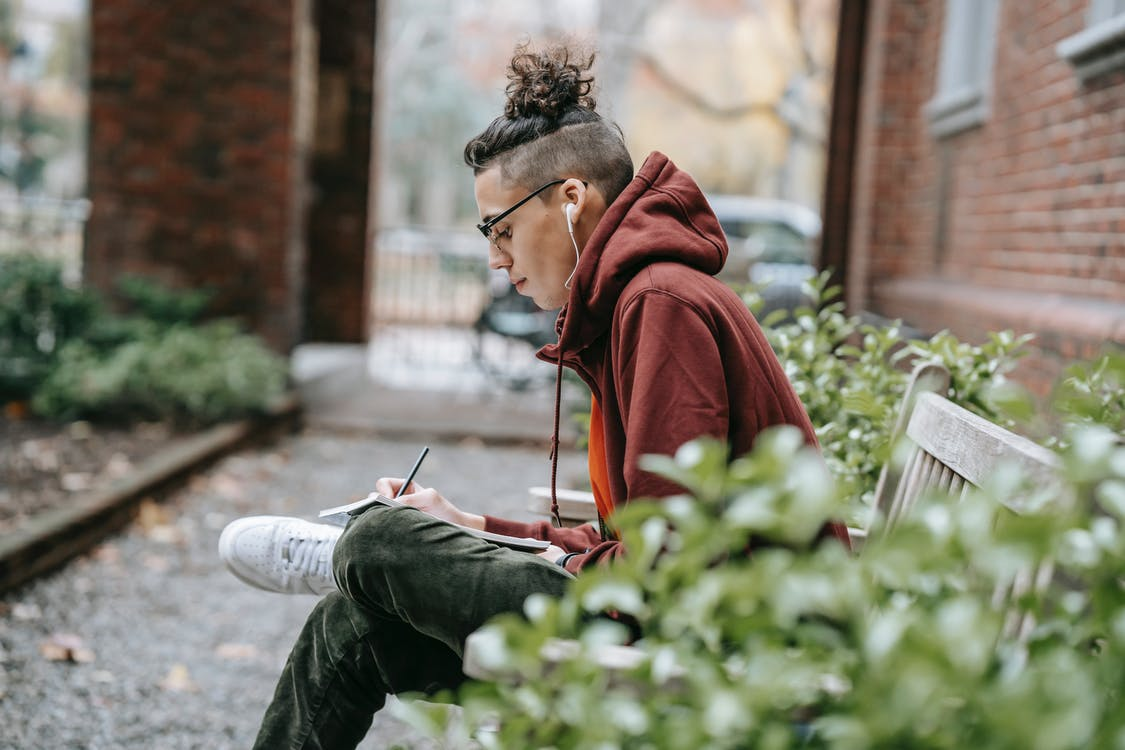 Young intelligent man with trendy hairstyle writing on paper