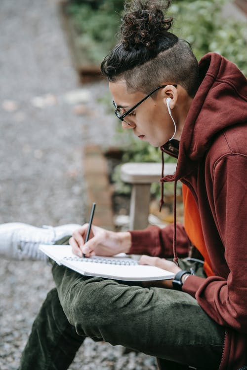 From above of intelligent student in earphones writing in notebook on blurred background of yard