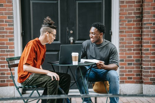 Cheerful multiracial friends discussing university at table with netbook and coffee near entrance of brick building