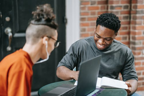 Happy young African American male student smiling and taking notes in copybook while preparing for exams with friend using laptop in street cafe