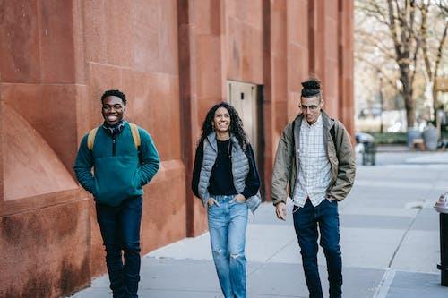 Happy diverse groupmates walking along street after studies