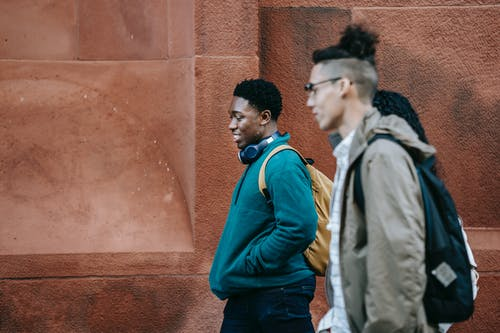 Smiling trendy diverse teens chatting and walking on street
