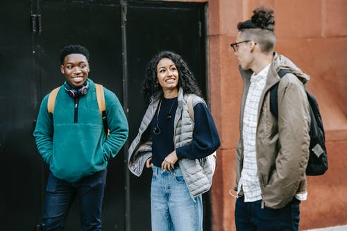 Cheerful multiracial young men and woman in stylish clothes and backpacks standing on street and communicating after studies