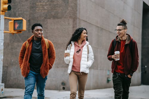 Happy young multiracial friends smiling while walking on street with takeaway coffee